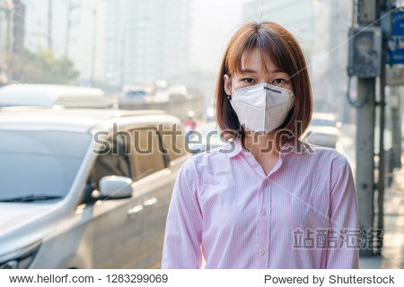 Asian woman wearing the N95 Respiratory Protection Mask against air pollution at road and traffic in Bangkok  healthcare concept