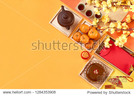 Chinese New Year decoration and food. Orange  tea  new year cake  red packet  fire cracker  plum blossom and lantern on color paper background. Translation of text appear in image: Prosperity