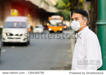 A man wearing mouth mask against air smog pollution with PM 2.5 in Bangkok city  Thailand.