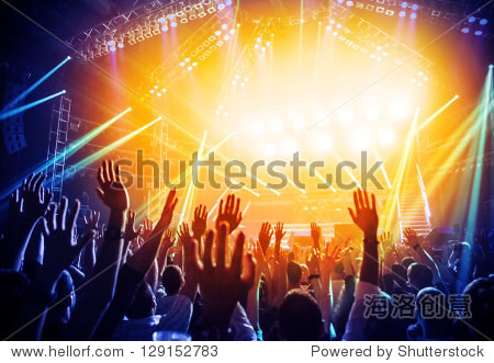 Photo of young people having fun at rock concert  active lifestyle  fans applauding to famous music band  nightlife  DJ on the stage in the club  crowd dancing on dance-floor  night performance