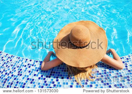 Pretty woman in a hat enjoying a swimming pool