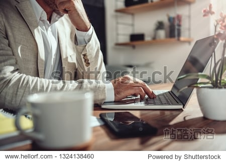 Businessman wearing linen suit sitting at his desk and using laptop in the office