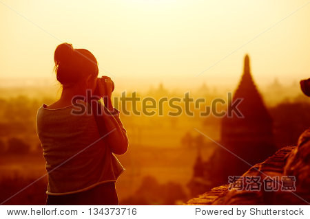 female traveler photographing temples at Bagan Myanmar Asia at sunrise