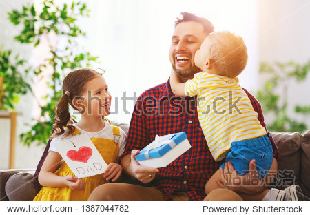 Happy father's day! Children congratulates dad and gives  him a gift and postcard
