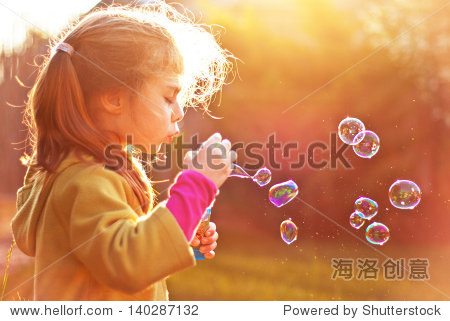 Five years old caucasian child girl blowing soap bubbles outdoor at sunset - happy carefree childhood