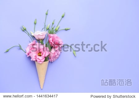 Beautiful composition with waffle cone and fresh flowers on color background