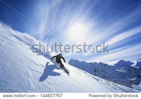 Full length of skier skiing on fresh powder snow