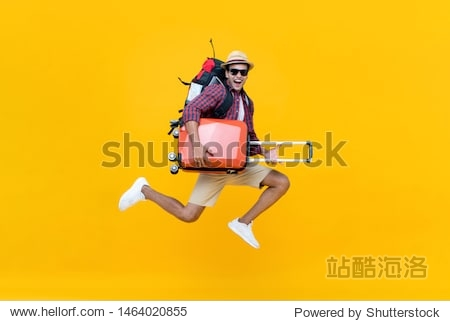 Excited happy young Asian man tourist with luggage jumping isolated on yellow studio background