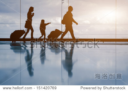 Silhouette of young family with luggage walking at airport  girl showing something through the window