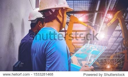 maintenance man checking and control the automation robot arms by using tablet in the factory  technology factory 4.0 concept