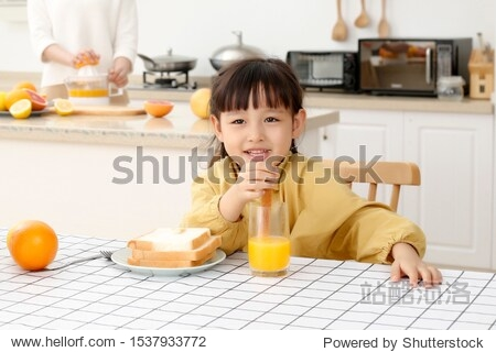 Asian little girl eating with orange juice and bread sticks
