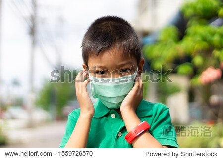 Asian child boy wearing a protection mask for prevent coughing and sneezing and his hands close his mouth. Healthy concept.
