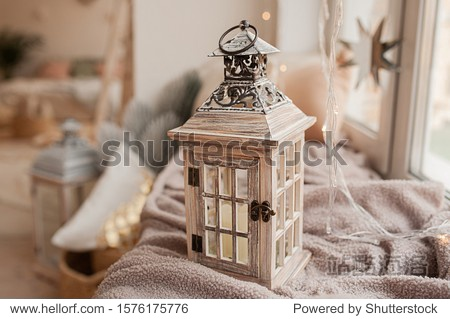 home decoration  wooden candlestick in the form of a street lamp on the background of a cozy interior in the style of boho