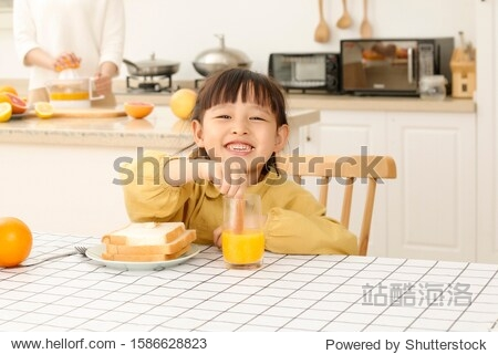 Asian little girl with bread sticks with juice smiles happily