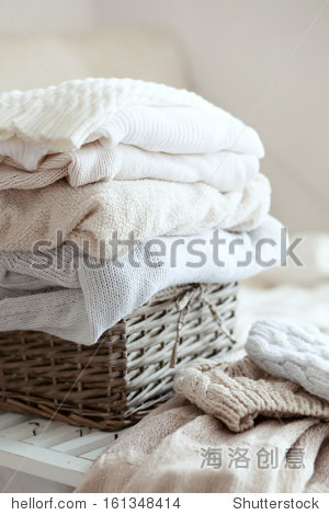 Stack of cozy knitted sweaters in wicker basket