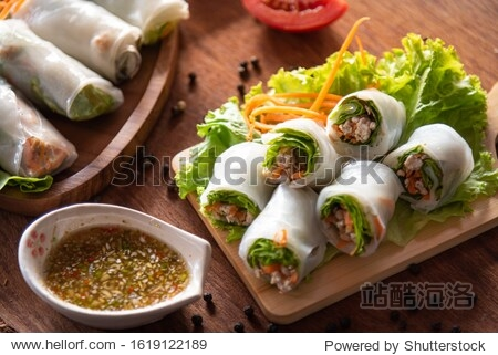 Asian spring rolls as portion stuff vegetable  pork inside noodle tubes on old wood plate with spicy sauce