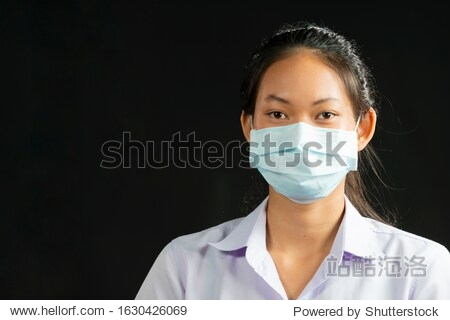Young Asian woman wearing facial hygienic mask for Safety on black background against infectious diseases  flu  anti-pollution  anti-smog and viruses. Space for text