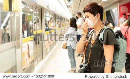 Beautiful middle aged Asian female traveller cover mouth and cough  wear medical face mask to protect from infection of viruses  pandemic  outbreak and epidemic of disease in crowded underground train