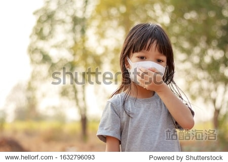 A long haired thai girl is wearing a gray shirt  standing outside  wearing a white mask  protecting his face from polluted airborne dust and wearing a mask to protect against germs and viruses.