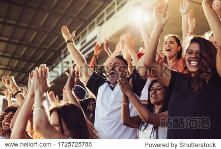 Crowd of sports fans cheering during a match in stadium. Excited people standing with their arms raised  clapping and yelling to encourage their team.