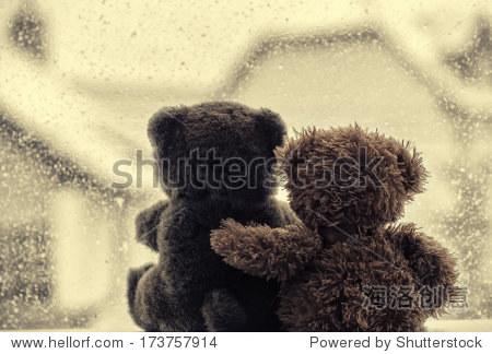Bears in love's embrace  sitting in front of a window
