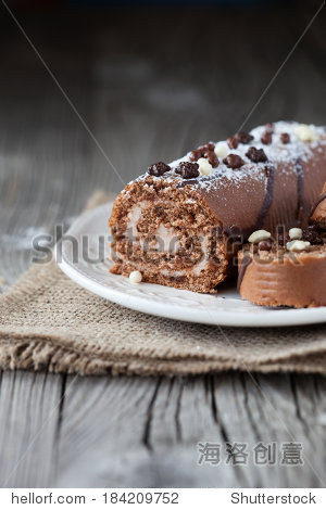 Chocolate cake roll with coffee cream on a wooden background  selective focus