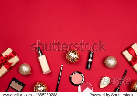 Makeup professional products flat lay on red background top view  copy space. Foundation  eyeshadows  blusher  sponge  mascara  lipstick  gift. Christmas cosmetic. Christmas shopping. Xmas celebration