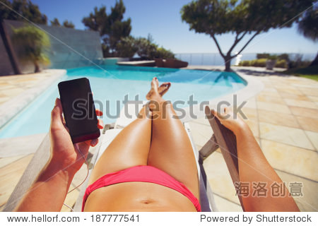 Young lady wearing bikini using mobile phone while sunbathing by the pool. Female model resting on a deckchair using smart phone.