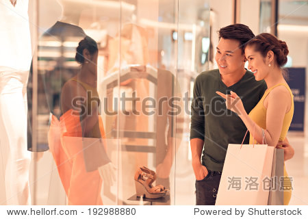 Young woman showing something in the shop window to her husband