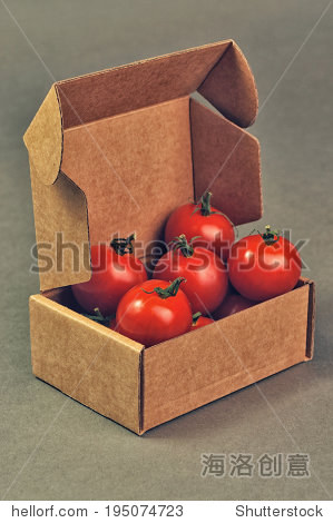 red small tomatoes close up in brown box
