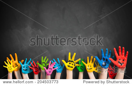 painted hands in front of a blackboard
