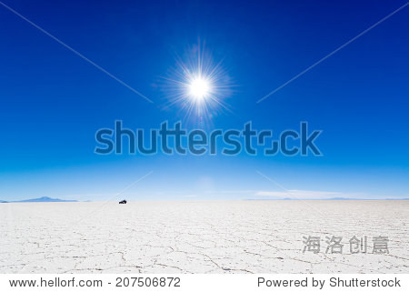 View of the sun over the Uyuni Salt Flats in Bolivia with an SUV in the background.