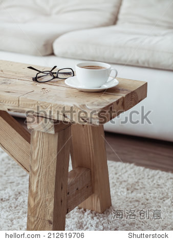 Still life details  cup of coffee on rustic bench over white sofa