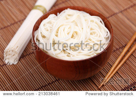 Bowl of rice noodles with chopsticks and raw rice noodles on bamboo napkin. Close-up.