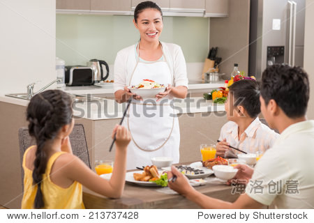 Vietnamese woman bringing dish to dinner table