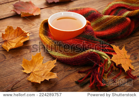 Cup of tea with autumn leaves reflection on book on wooden table. Season of Education