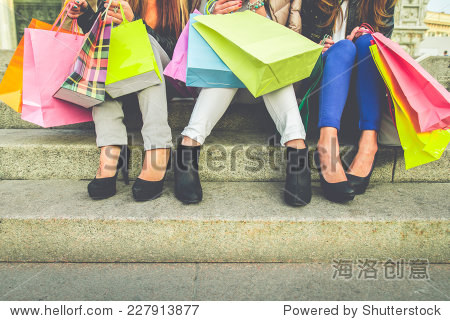 Women with high heels and shopping bags - Three girls sitting on stairs and chatting after buying presents