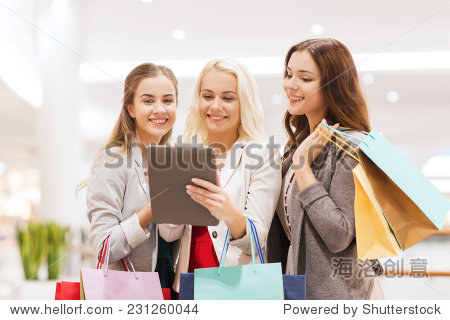 sale  consumerism  technology and people concept - happy young women with tablet pc and shopping bags in mall
