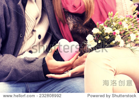 A midsection of a romantic couple sitting on a bench in the park holding Valentines gift and flowers