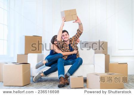 Dream come true  moving. Loving couple enjoys a new apartment and keep the box in his hands while young and beautiful couple in love sitting on the couch in an empty apartment among boxes