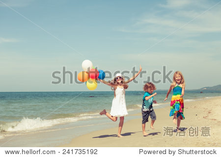 Three happy children with balloons  dancing on the beach at the day time