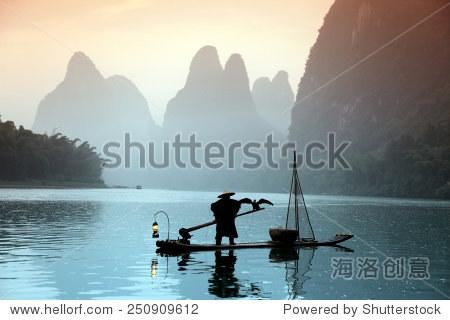 Chinese man fishing with cormorants birds in Yangshuo, China
