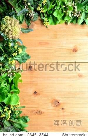Spring green leaf vegetables.frame.on white wooden background