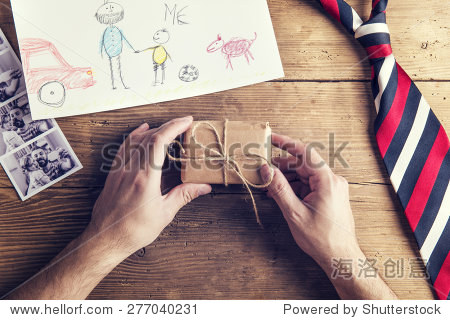 pictures of father and daughter  childs drawing  present and tie laid on wooden desk backround.