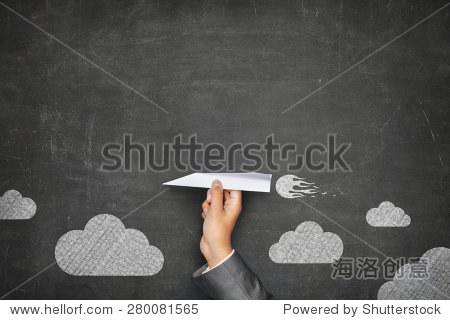 Businessman hand holding paper plane on front of vintage full frame black blank blackboard no frame and couple clouds