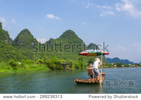 Bamboo rafting in the Yulong River surrounded by dramatic landscape of limestone karst.