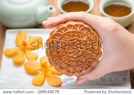 Chinese mid autumn festival foods. Traditional mooncakes on table setting with teacup.  Hand holding a mooncake