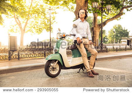 Portrait of a handsome man leaning on scooter outdoors