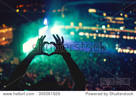 Heart shaped hands at concert  loving the artist and the festival. Music concert with lights and silhouette of a man enjoying the concert