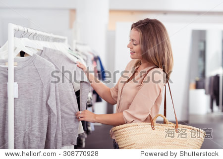 Half Body Shot of a Happy Young Woman with Shoulder Bag Looking at Clothes Hanging on the Rail Inside the Clothing Shop.